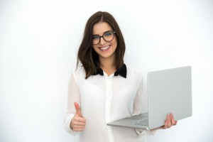Smiling businesswoman standing with laptop and showing thumb up