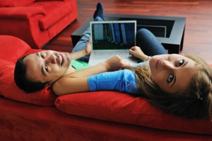 happy young couple have fun and relax at comfort bright appartment and work on laptop computer
